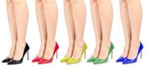 Metta le scarpe del tacco alto sulle gambe della donna isolate Immagine Stock