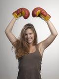 Metta in mostra i guantoni da pugile della giovane donna, fronte dello sho dello studio della ragazza di forma fisica Fotografie Stock Libere da Diritti