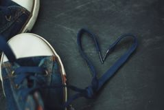 Metta in mostra i pizzi di forma del cuore dei bambini degli stivali delle blue jeans sopra Grounge strutturato Chalckboard modif fotografia stock libera da diritti