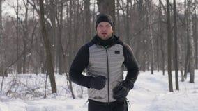 Metta in mostra il funzionamento dell'uomo nel parco della città dell'inverno durante il trotto di mattina Pareggiando nella fore immagine stock