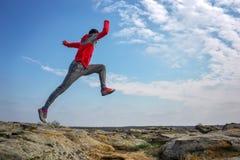 Metta in mostra il funzionamento dell'uomo, saltante sopra le rocce nella zona di montagna Immagine Stock