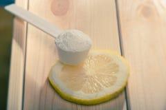 Metta in mostra il supplemento o la vitamina con una fetta del limone Concetto di nutrizione di sport Fotografia Stock Libera da Diritti
