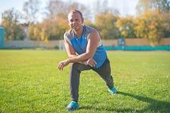 Metta in mostra l'uomo che allunga al parco, facente si esercita su erba Concetti di forma fisica Fotografia Stock Libera da Diritti