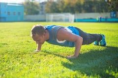 Metta in mostra l'uomo che allunga al parco, facente spinta-UPS su erba un il giorno soleggiato Concetti di forma fisica Fotografia Stock