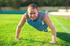 Metta in mostra l'uomo che allunga al parco, facente spinta-UPS su erba un il giorno soleggiato Concetti di forma fisica Fotografia Stock Libera da Diritti
