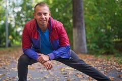 Metta in mostra l'uomo che allunga all'autunno del parco, facente gli esercizi Concetti di forma fisica Immagini Stock