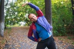 Metta in mostra l'uomo che allunga all'autunno del parco, facente gli esercizi Concetti di forma fisica Fotografia Stock