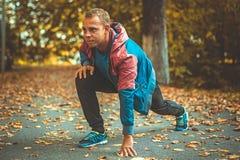 Metta in mostra l'uomo che allunga all'autunno del parco, facente gli esercizi Concetti di forma fisica Fotografie Stock Libere da Diritti