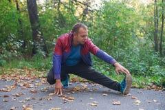Metta in mostra l'uomo che allunga all'autunno del parco, facente gli esercizi Concetti di forma fisica Immagini Stock Libere da Diritti