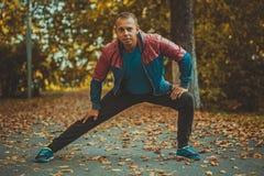 Metta in mostra l'uomo che allunga all'autunno del parco, facente gli esercizi Concetti di forma fisica Immagine Stock Libera da Diritti