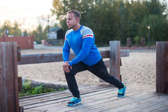 Metta in mostra l'uomo che allunga i aoutdoors che fanno gli esercizi che anche al tramonto Concetti di forma fisica Fotografia Stock Libera da Diritti