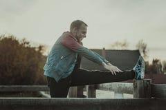 Metta in mostra l'uomo che allunga i aoutdoors che fanno gli esercizi che anche al tramonto Concetti di forma fisica Immagini Stock Libere da Diritti