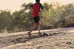 Metta in mostra l'uomo con le gambe atletiche e muscolari strappate che corre in salita fuori dalla strada nell'allenamento pareg Fotografie Stock