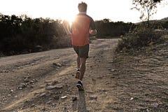 Metta in mostra l'uomo con le gambe atletiche e muscolari strappate che corre in salita fuori dalla strada nell'allenamento pareg immagini stock libere da diritti