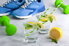 Metta in mostra la composizione con acqua di vetro dell'articolo sportivo con il limone m. Fotografie Stock Libere da Diritti