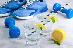 Metta in mostra la composizione con acqua di vetro dell'articolo sportivo con il limone m. Fotografia Stock Libera da Diritti