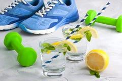 Metta in mostra la composizione con acqua di vetro dell'articolo sportivo con il limone m. Immagini Stock Libere da Diritti