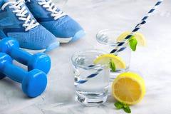 Metta in mostra la composizione con acqua di vetro dell'articolo sportivo con il limone m. Immagine Stock