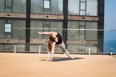 Metta in mostra la donna che fa allungando l'esercizio di yoga sul tetto dell'hotel con il cavalletto di legno sulla stuoia di yo Immagini Stock
