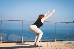 Metta in mostra la donna che fa allungando l'esercizio di yoga sul tetto dell'hotel con il cavalletto di legno sulla stuoia di yo Fotografie Stock