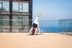 Metta in mostra la donna che fa allungando l'esercizio di yoga sul tetto dell'hotel con il cavalletto di legno sulla stuoia di yo Fotografia Stock