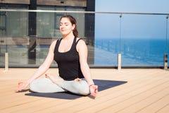 Metta in mostra la donna che fa allungando l'esercizio di yoga sul tetto dell'hotel con il cavalletto di legno sulla stuoia di yo Immagine Stock