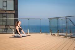 Metta in mostra la donna che fa allungando l'esercizio di yoga sul tetto dell'hotel con il cavalletto di legno sulla stuoia di yo Immagini Stock Libere da Diritti