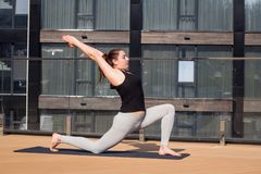 Metta in mostra la donna che fa allungando l'esercizio di yoga sul tetto dell'hotel con il cavalletto di legno sulla stuoia di yo Immagine Stock Libera da Diritti