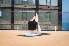 Metta in mostra la donna che fa allungando l'esercizio di yoga sul tetto dell'hotel con il cavalletto di legno sulla stuoia di yo Fotografia Stock Libera da Diritti