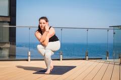 Metta in mostra la donna che fa allungando l'esercizio di yoga sul tetto dell'hotel con il cavalletto di legno sulla stuoia di yo Fotografie Stock Libere da Diritti