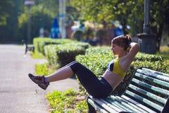 Metta in mostra la donna che fa gli esercizi durante l'allenamento all'aperto di addestramento trasversale Fotografia Stock Libera da Diritti