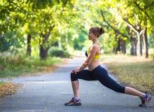Metta in mostra la donna che fa gli esercizi durante l'allenamento all'aperto di addestramento trasversale Fotografie Stock