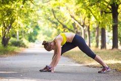 Metta in mostra la donna che fa gli esercizi durante l'allenamento all'aperto di addestramento trasversale Fotografia Stock