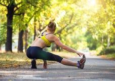 Metta in mostra la donna che fa l'allungamento durante l'allenamento all'aperto di addestramento trasversale Fotografia Stock Libera da Diritti