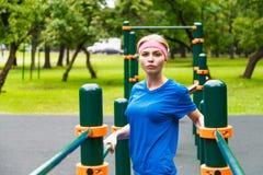 Metta in mostra la donna che fa l'allungamento prima dell'correre nel parco Immagini Stock