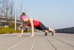 Metta in mostra la donna che fa spinta-UPS fuori sulla banchina della città di mattina Fotografia Stock