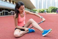 Metta in mostra la donna che utilizza il bastone del rullo sulle gambe nello stadio di sport Fotografia Stock Libera da Diritti