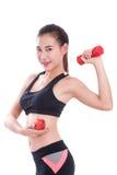 Metta in mostra la donna con i pesi di sollevamento e mela di tenuta Fotografie Stock Libere da Diritti