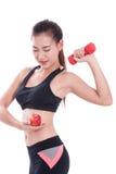 Metta in mostra la donna con i pesi di sollevamento e mela di tenuta Fotografie Stock