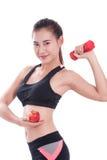 Metta in mostra la donna con i pesi di sollevamento e mela di tenuta immagini stock