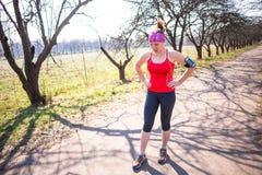 Metta in mostra la donna di forma fisica che fa l'allenamento all'aperto di addestramento trasversale al giorno soleggiato Immagini Stock Libere da Diritti