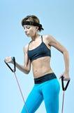 Metta in mostra la donna di forma fisica che fa l'esercizio con l'allungamento dell'estensore Immagine Stock