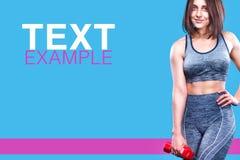 Metta in mostra la donna di forma fisica che fa l'esercizio con le teste di legno rosse vicino ad una parete blu Copi lo spazio p Fotografia Stock