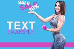 Metta in mostra la donna di forma fisica che fa l'esercizio con le teste di legno rosse vicino ad una parete blu Copi lo spazio p Fotografie Stock Libere da Diritti
