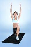 Metta in mostra la donna di forma fisica che fa l'esercizio su una stuoia nera della palestra immagini stock