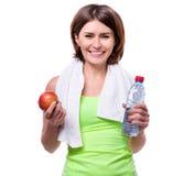 Metta in mostra la mela e l'acqua della tenuta della ragazza con l'asciugamano sul suo collo fotografie stock