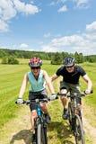 Metta in mostra la montagna che biking - uomo che spinge la ragazza Fotografia Stock Libera da Diritti