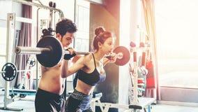 Metta in mostra la ragazza che fa gli esercizi del peso che lavorano con i bilancieri pesanti Fotografie Stock