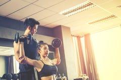 Metta in mostra la ragazza che fa gli esercizi del peso che lavorano con le teste di legno pesanti Fotografia Stock Libera da Diritti