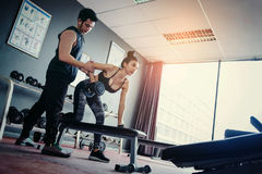 Metta in mostra la ragazza che fa gli esercizi del peso che lavorano con le teste di legno pesanti h Immagine Stock